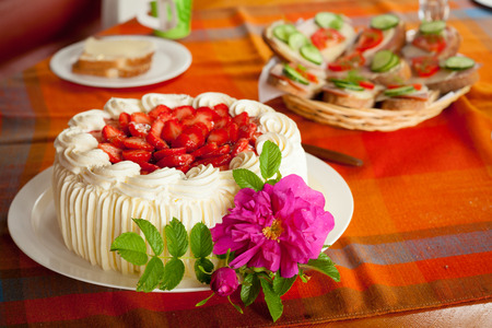 Delicious strawberry cake on coffee table photo