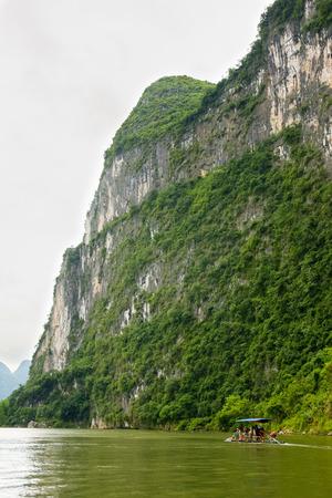 Big limestone cliff and bamboo boat on Li river china photo