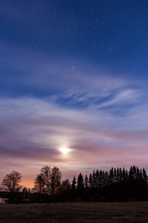 Night landscape and cloudy starry sky and moon photo