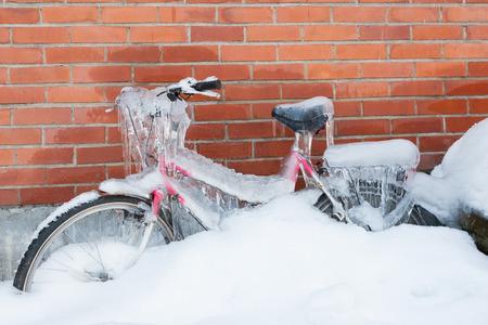 Bevroren ijs bedekt fiets leunend tegen de muur Stockfoto