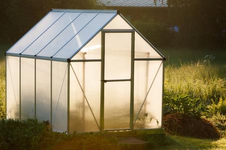 Kleine kas in de achtertuin in een gouden licht van de dageraad
