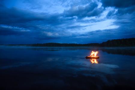 Kampvuur op het meer Stockfoto