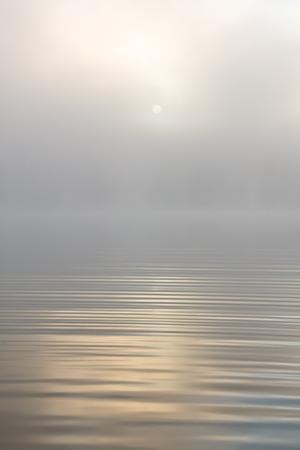 Ochtendzon door mist op het meer