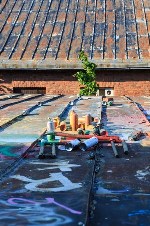abandoned warehouse: Used graffiti spray cans laying around at roof of abandoned warehouse