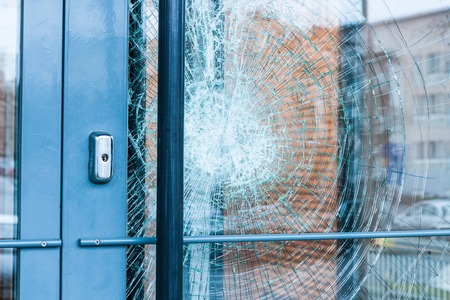 damaged: Broken glass front door outside Stock Photo