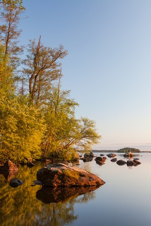 scenic  landscape: Calm lakeside at sunset and rocks on the water