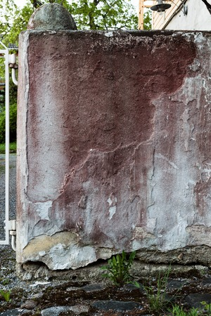 irregularity: Old broken concrete wall and faded red paint