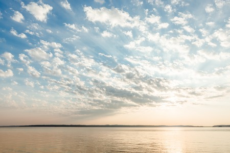 Beautiful clouds and sun rays over lake at sunrise Banque d'images