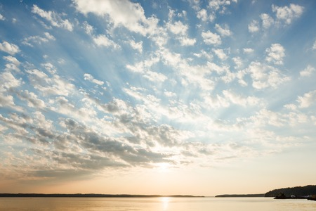 Beautiful clouds and sun rays over lake at sunrise Foto de archivo