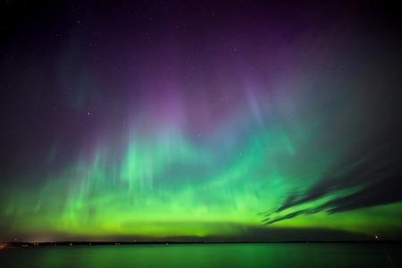 scenic  landscape: Beautiful northern lights aurora borealis over lake in finland Stock Photo