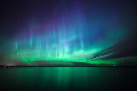 Światła: Piękne zorza polarna Aurora Borealis nad jeziorem w Finlandii