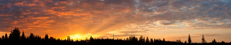 traquil scene: Cloudscape panorama of sunrise over forest in finland Stock Photo
