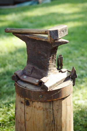 medieval blacksmith: Worn iron anvil and hammer outdoors Stock Photo