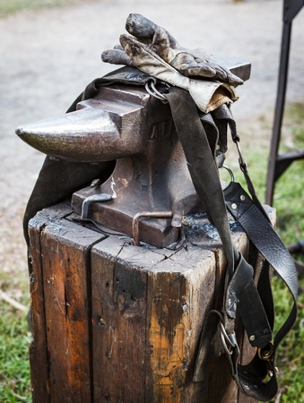 medieval blacksmith: Worn iron anvil apron and gloves outdoor