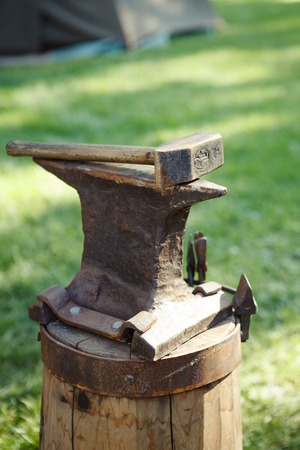 anvil: Worn iron anvil and hammer outdoors Stock Photo