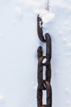 partially: Strong chain partially buried in snow close-up