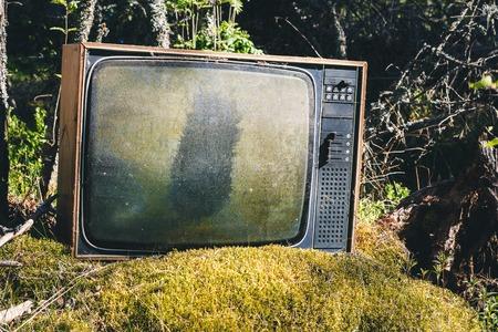 Oude verlaten analoge televisie in bos