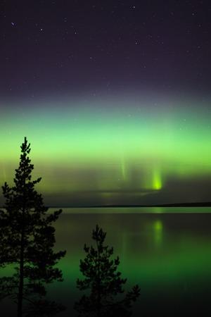 Beautiful northern lights aurora borealis over lake in finland Reklamní fotografie