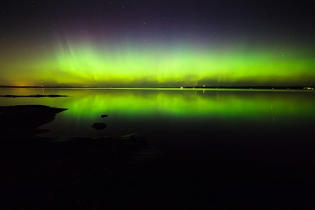 geomagnetic: Beautiful northern lights aurora borealis over lake in finland Stock Photo