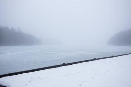 frozen lake: Thick fog at frozen lake and forest landscape