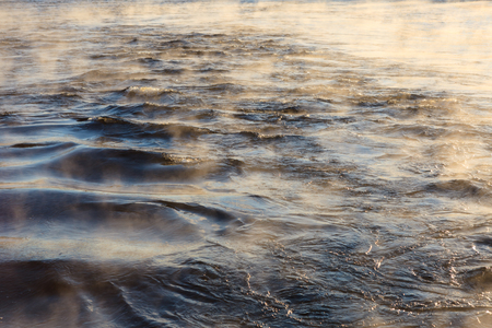 water vapor: Water vapor on surface of cold icy water at sunny cold winter day