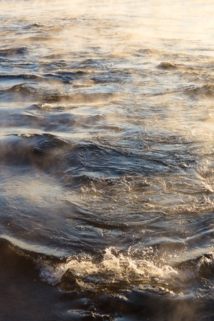 evaporate: Water vapor on surface of cold icy water at sunny cold winter day