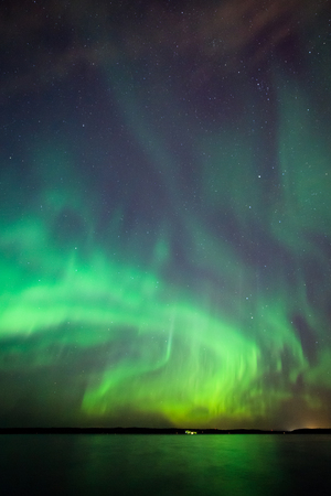 Beautiful northern lights aurora borealis over lake in finland Stock Photo