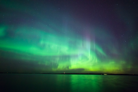 Beautiful northern lights aurora borealis over lake in finland Imagens