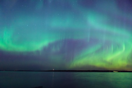 long lake: Beautiful northern lights aurora borealis over lake in finland Stock Photo