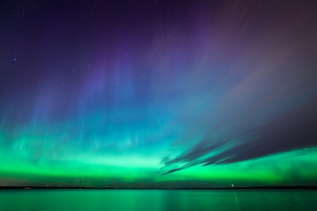 ionosphere: Beautiful northern lights aurora borealis over lake in finland Stock Photo
