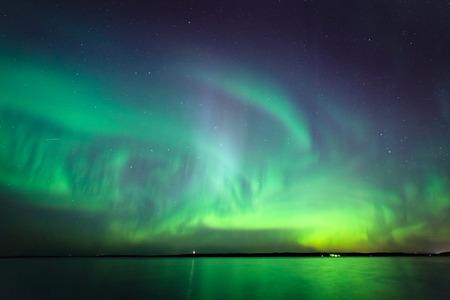Mooie noorderlichtaurora borealis over meer in Finland