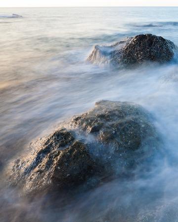 Waves and rocks shore long exposure Stock Photo