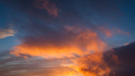 illuminated: Sunset colors at cloud sky Stock Photo