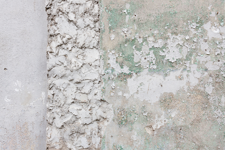 Aged concrete wall with cracked plaster