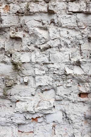 worn structure: Broken old white brick wall