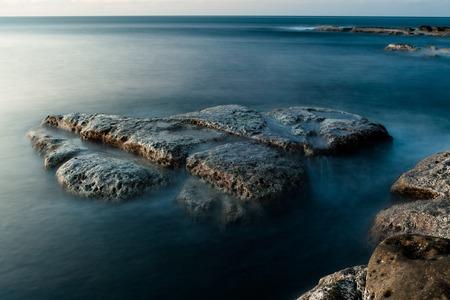 Rocks at shore long exposure landscape Stock Photo