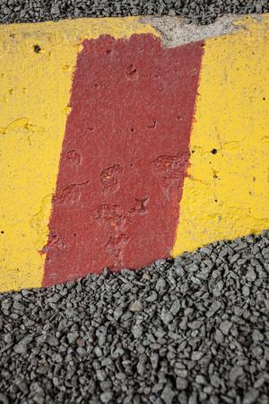 Worn concrete roadblock in gravel
