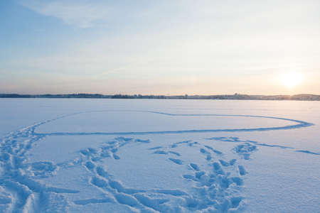 Heart shape made in snow by walking at frozen lake Banque d'images - 115105239
