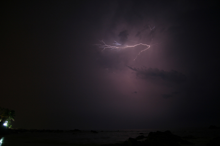 Small lightning strike in sky at clouds Stock Photo