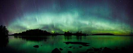 Beautiful northern lights aurora borealis over lake in Finland panorama