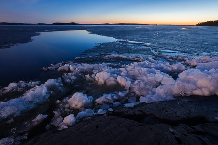 Partially melting ice in lake at night landscape