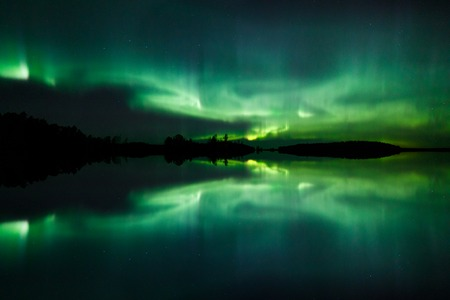 Beautiful northern lights aurora borealis over lake in Finland Фото со стока