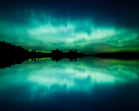 Beautiful northern lights aurora borealis over lake in Finland 스톡 콘텐츠