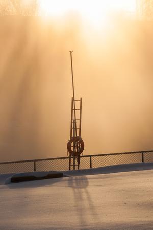 Street light at foggy winter morning in city park