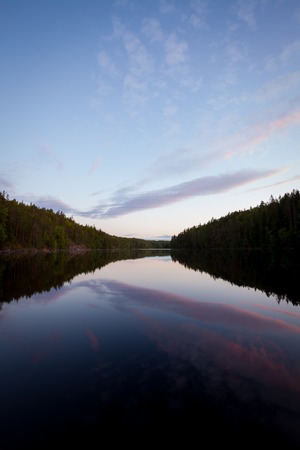 Sky reflecting from calm forest lake at midsummer night in Finland Stockfoto