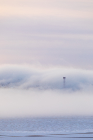 Dreamy thick fog at sunrise over hill and city buildings 版權商用圖片