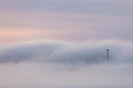 Dreamy thick fog at sunrise over hill and city buildings Zdjęcie Seryjne