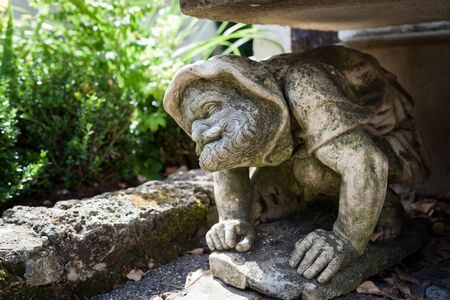 Funny looking human statue crouching under bench in garden