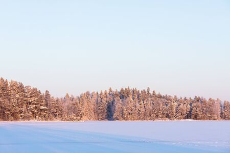Winter forest island at forzen lake sunset landscape Stock Photo