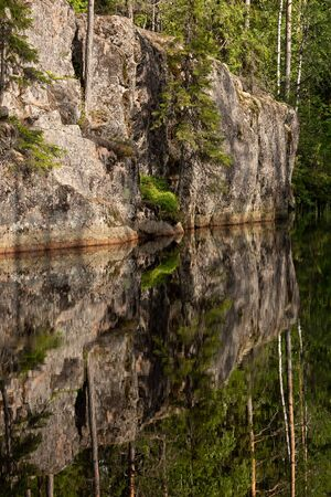 Rock reflectin to still water abstract in forest lake Banco de Imagens